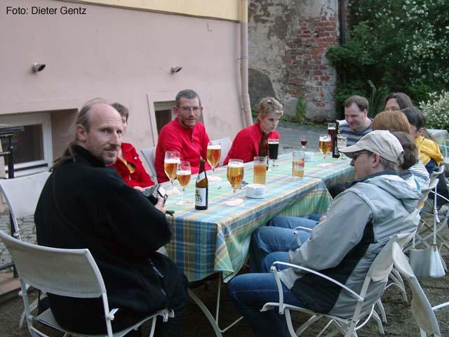 Foto: Die Gruppe sitzt an einem langen Tisch mit Gläsern vor sich, die größtenteils mit Bier gefüllt sind.