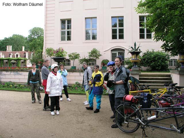 Die Gruppe hat die Tandems neben dem Branitzer Schloss abgestellt und macht sich auf den Weg die Außenanlagen des im Hintergrund zu sehenden Schlosses zu besichtigen. Eine Treppe mit 8 Stufen führt  auf das Podest, auf dem das Schloss steht.