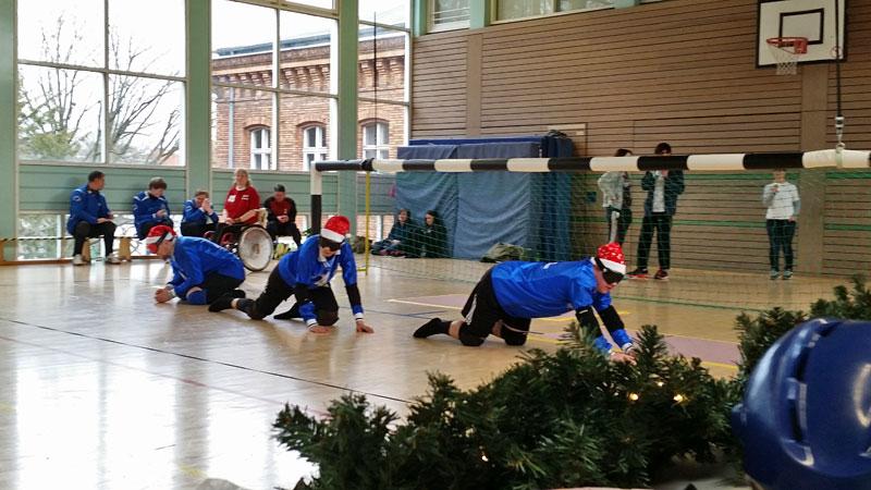 Foto: Blick von der Seite auf das Spielfeld. 3 Spieler in blau-schwarzen Trikot und rot-weißen Nikolausmützen auf dem Kopf knien vor dem Tor und lauschen auf den Ball.