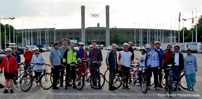 Foto: Im Vordergrund steht die Gruppe mit 10 Tandems auf dem Olympischen Platz, im Hintergrund ist der Haupteingang des Berliner Olympiastadions zu sehen: Das Olympisches Tor ist von zwei Türmen eingerahmt, zwischen denen in luftiger Höhe die olympischen Ringe hängen.