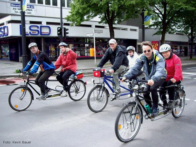 Foto: Die Tandemgruppe, vertreten durch drei Tandems, unterwegs auf der Bismarckstraße, an der Ecke Kaiser-Friedrich-Straße in Charlottenburg. Die Route führte weiter Richtung Osten zum Ernst-Reuter-Platz. Der Regen machte gerade Pause, leider nicht mehr lange. Dank für Autos gesperrter Straßen lässt es sich bequem nebeneinander radeln. Links hinten fahren Thomas und Thorsten - Thorsten winkt dem Fotografen zu. In der Mitte sind Hans-Jörg und Liane zu sehen, rechts vorne Herbert und Gisela.