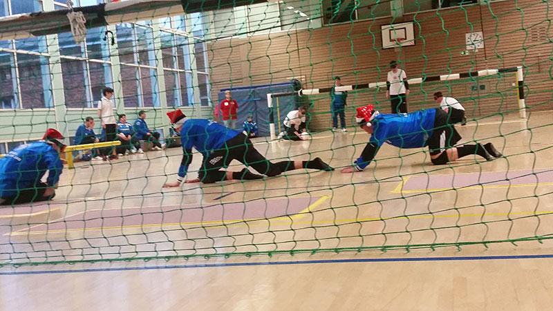 Foto: Blick durch das Tor aufs Spielfeld: die 3 Spieler mit den Nikolausmützen knien nun vor dem Tor. Im Hintergrund die Mannschafft des BBSV,           ein Spieler hat den Ball in der Hand.